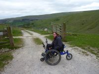 A wheelchair user on a track tin the countryside.